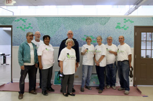 Riimland staff and volunteers pose in front of the mural.