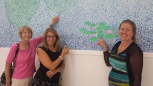 (L to R) Artist and mural designer Katy Ingle with volunteer painters Nancy Crane and Sherryanne de la Boise pointing to the sections they each painted.