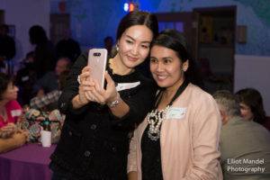 Anniversary committee member Nina Yoo takes a selfie with a friend.