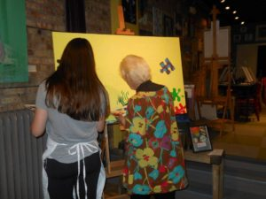 Bottle and Bottega guests work on the mural.